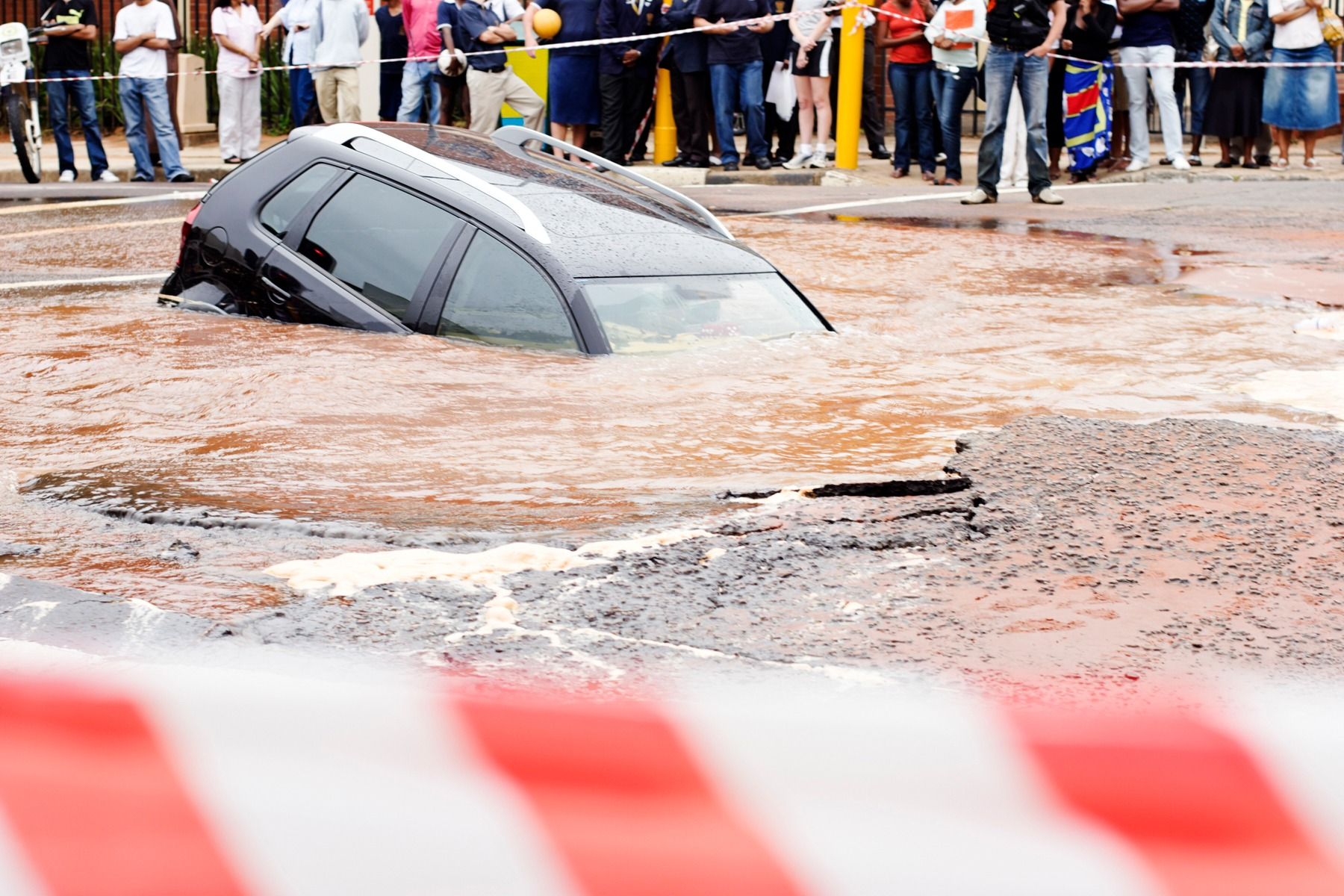 SUV is submerged in water in a large pothole